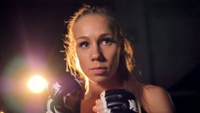 En blond kämpe i makrosikt lyfter hennes nävar Kvinnakämpestående HD lager videofilmer