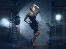 En blond kvinna i en klänning som poserar i en studio Royaltyfria Foton