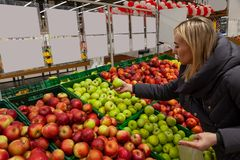 En blond kvinna i en supermarket köper äpplen, lutar skilja sig åt igenom arkivfoton