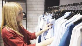 En blond kvinna som väljer kläder i en shoppavisningslokal royaltyfri foto