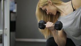 En blond kvinnaidrottsman nen som gör övning på bicepens arkivfilmer