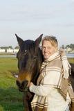 En blond man med hans bruna häst. Arkivfoto