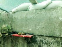 En bloque del ejército con el arma automática y la granada del casco fotografía de archivo