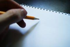 En blyertspenna, en hand för tomt ark Arkivbilder