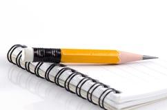 En blyertspenna och en anteckningsbok Royaltyfri Fotografi