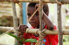 En blyg men nyfiken västra papuanflicka som ser till och med staketet Royaltyfri Foto