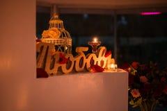 ` En bois d'amour de ` d'inscription près des bougies brûlantes romantique Image stock