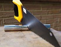 En bois a vu utilisé pour couper une pipe en métal Photo stock