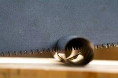 En bois a vu utilisé pour couper une pipe en métal Photos libres de droits