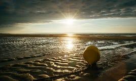 En boj vid havet i lågvatten i panelljus med en molnig himmel och en inställningssol Royaltyfria Bilder