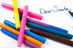En bokstav till Santa Claus och färgrika pennor på förgrunden Arkivfoto