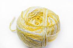 En boll av den vita och gula tråden Begreppet av handarbete som sticker royaltyfria foton