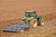 En bonde med en traktor som plogar landet, innan att så 072 Arkivbild