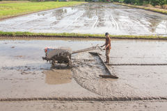 En bonde plogar med traktoren Fotografering för Bildbyråer