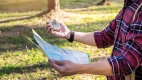 en borttappad turist i en vandring med kompasset som siktar riktningen i th Fotografering för Bildbyråer