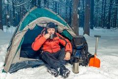 En borttappad turist i vinterskogen som dricker te, medan sitta I Arkivfoto