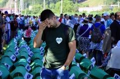 En bosnisk muslimsk man sitter och gråter nära kistan av hans släkting på en minnes- mitt i Potocari Royaltyfri Foto