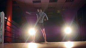 En boxare utbildar på ett tomt idrottshallgolv under strålkastare stock video