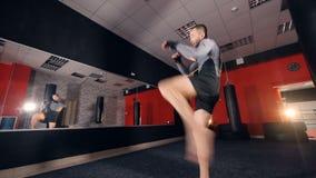 En boxare utbildar vid honom nära en idrottshallspegel lager videofilmer