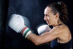 En boxarekvinna kastar en nävenäve i säcken Royaltyfri Foto