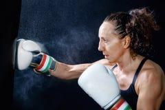 En boxarekvinna kastar en nävenäve i säcken Arkivbilder