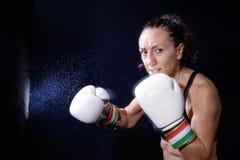 En boxarekvinna kastar en nävenäve i säcken Fotografering för Bildbyråer