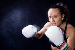 En boxarekvinna kastar en nävenäve i säcken Arkivbild