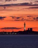 En brännhet röd solnedgång inramniner en uddtorskplats arkivfoto