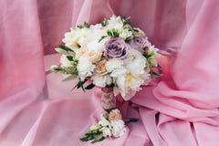 En bröllopbukett av kräm- pioner och purpurfärgade rosor är på en rosa kanfas Royaltyfri Foto