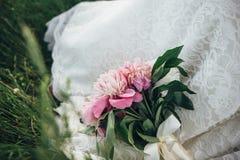 En bröllopbukett av pions som binds med kräm- lögner för ett band på klänningen för brud` s Arkivbilder