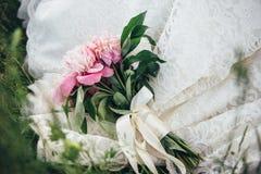 En bröllopbukett av pions som binds med kräm- lögner för ett band på klänningen för brud` s Royaltyfri Fotografi