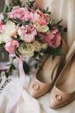 En bröllopbukett av rosa pioner, vita rosor och eukalyptus, förutom beigea skor för kvinna` s Royaltyfri Foto