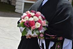 En bröllopbukett av vita och rosa rosor i händerna av en kvinna Arkivfoto