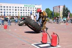 En brandman i en brandsäker dräkt kör och vänder ett stort rubber rullar in en konkurrens för slåss för brand, Vitryssland, Minsk royaltyfri foto