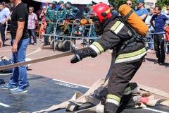 En brandman i en brandsäker dräkt och en hjälm som rymmer en brandslang på en brandsportkonkurrens Minsk Vitryssland, 08 07 2018 royaltyfri fotografi