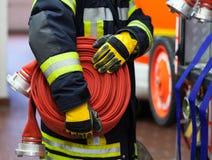 En brandman med vattenslangen royaltyfri bild
