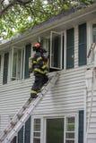 En brandman på brandplats framme av en byggnad Arkivbild