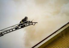 En brandman sätter ut en brinnande byggnad med höjdförlängningsstegar royaltyfria bilder
