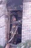 En brandman som gör rengöringsoperationer royaltyfria bilder