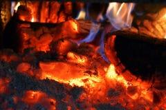 En brinnande brand med flammor, kol, askaen och rök royaltyfria foton