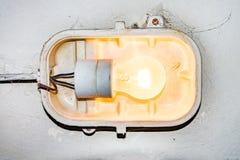 En brinnande lampa som hänger på en gammal splittrad vägg arkivfoton