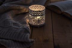 En brinnande stearinljus, en stucken tröja och en öppen bok på en wood tabell Royaltyfri Fotografi