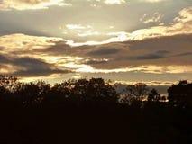 En bristning av ljusa bakifrån moln Arkivfoto