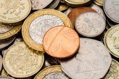 En brittisk encentmynt för singel överst av en hög av Coins Arkivfoton