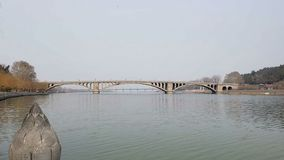 En bro över floden i det bleka höstlandskapet royaltyfria foton