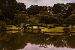 En bro över sjön som förbinder grönt gräs och land med träd under en blå himmel royaltyfri bild
