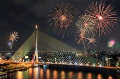 En bro med härliga fyrverkerier för beröm på skymningsi Royaltyfri Fotografi