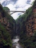 En bro på kanjonen och vattenfallet med solig blå himmel Fotografering för Bildbyråer