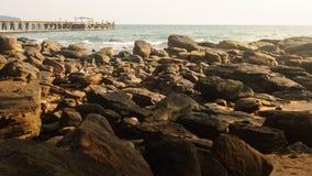 En bro till havet och en strand av vaggar mycket i aftonen Royaltyfri Fotografi