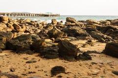 En bro till havet och en strand av vaggar mycket i aftonen Royaltyfria Foton